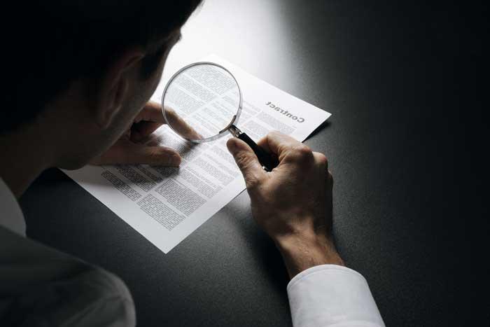 лупа, человек разглядывает документы, договор